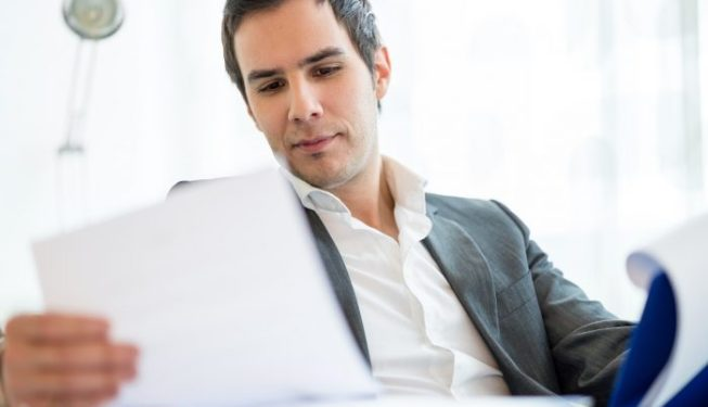 Close up Handsome Young Businessman Reviewing Business Documents at his Table Inside the Office.