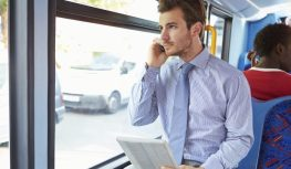 Businessman Using Mobile Phone And Digital Tablet On Bus