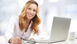 Close-up ortrait of executive business woman with laptop working on presentation.