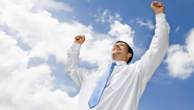 Portrait of happy businessman raising his hands with cloudy sky above him