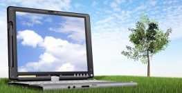 laptop computer on the grass outdoors with a blue sky in the background