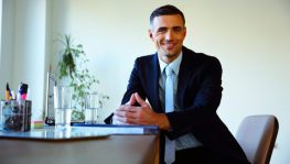 Happy businessman sitting at the table in office